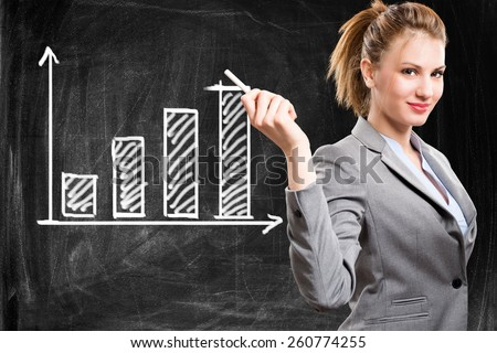 Smiling woman showing a positive business trend on a blackboard - stock photo