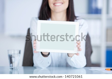 Smiling woman showing a tablet against the blurred background - stock photo