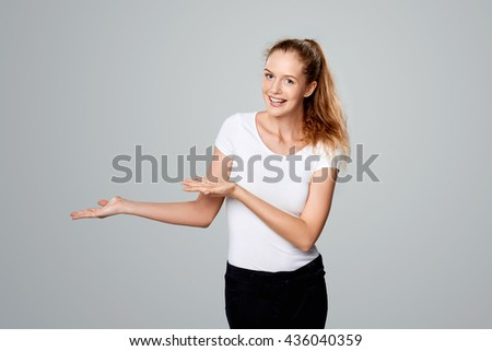 Smiling woman showing open hand palm with copy space for product or text looking at the camera - stock photo