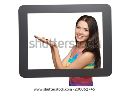 Smiling woman showing open hand palm with copy space for product or text, standing behind tablet frame - stock photo