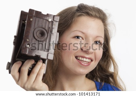 Smiling Woman shows old camera - stock photo