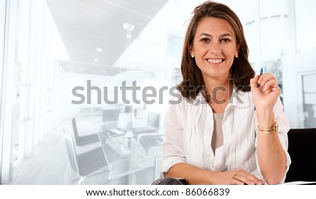 Smiling woman sitting at her desk on an office environment