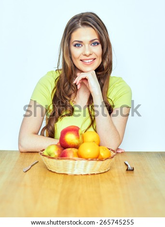 smiling woman sitting at the wooden table with apples,  oranges.healthy life style portrait.