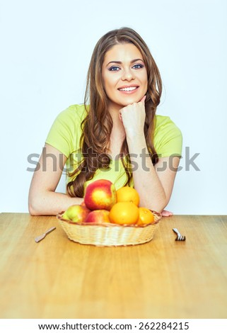 Smiling woman sitting at the wooden table with fruit. Vegetarian diet concept.