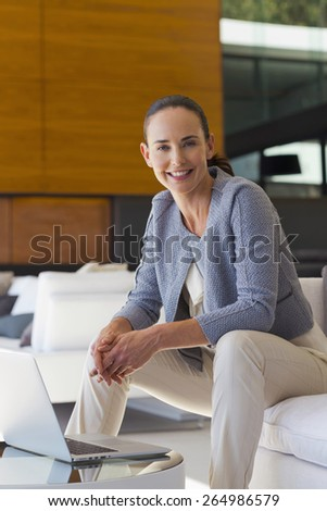 Smiling woman sitting in a sofa with laptop on coffee table. Close view. - stock photo