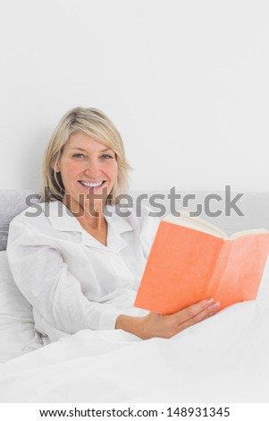 Smiling woman sitting in bed reading orange book at home in bedroom - stock photo
