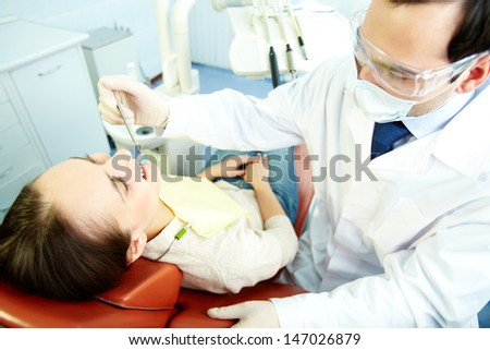 Smiling woman sitting in dentist�¢??s chair while doctor examining her teeth - stock photo