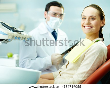 Smiling woman sitting in dentist�¢??s chair with doctor on background - stock photo