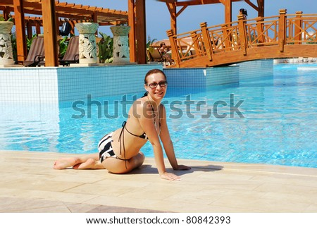 Smiling woman sitting near swimming pool at summer resort - stock photo