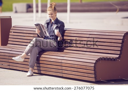 Smiling woman sitting on a bench with coffee and reading magazine - stock photo