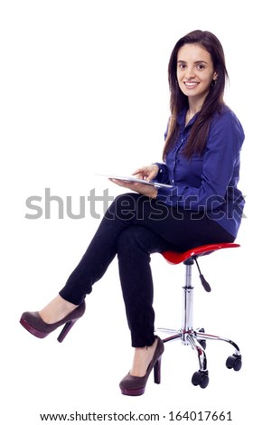 Smiling woman sitting on a chair with a tablet computer, isolated on white background - stock photo