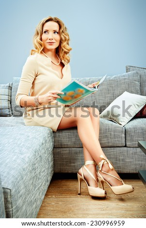 Smiling woman sitting on a couch in the living room. - stock photo