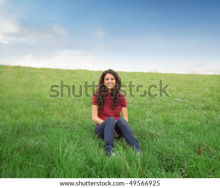 Smiling woman sitting on a green meadow - stock photo