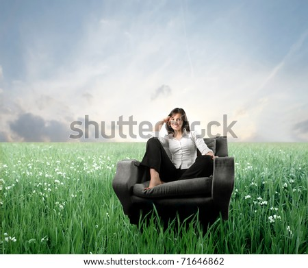 Smiling woman sitting on an armchair on a green meadow - stock photo
