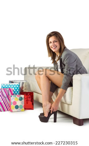 Smiling woman sitting on couch taking off her shoes at home in the living room - stock photo