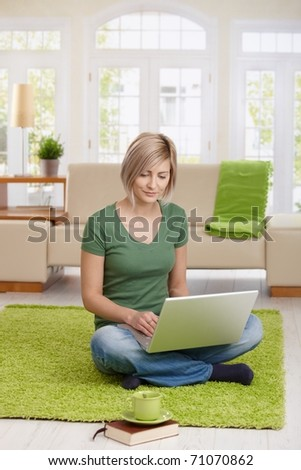Smiling woman sitting on floor at home in living room using laptop computer for teleworking.? - stock photo