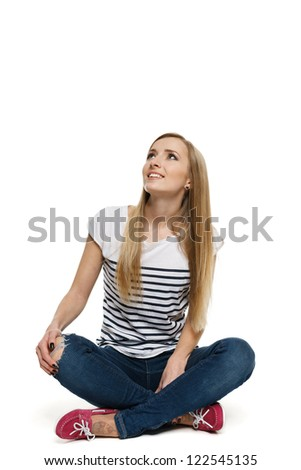 Smiling woman sitting on floor looking up at bank copy space, over white background - stock photo