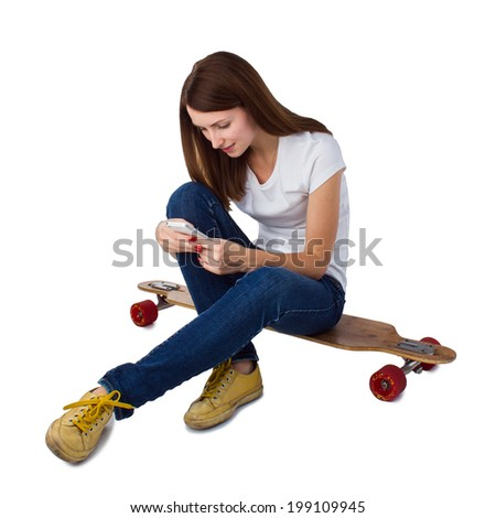 Smiling woman sitting on skateboard and using smart phone. Isolated on a white background.