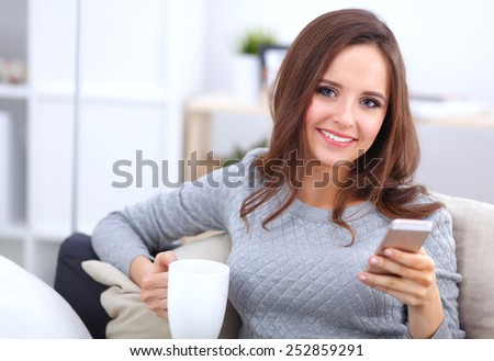 Smiling woman sitting on sofa holding coffee using phone