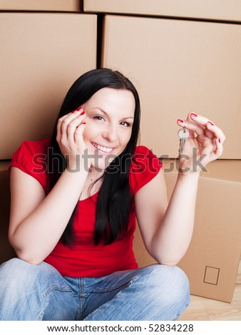 smiling woman sitting with cartons and holding keys to flat - stock photo
