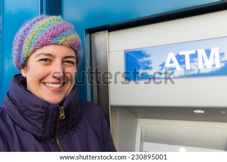 Smiling woman standing at an ATM wearing a woolen hat - stock photo