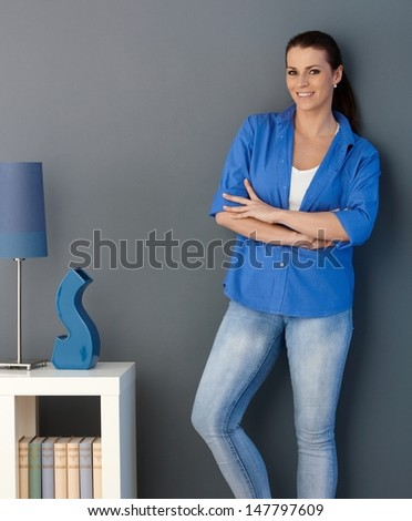 Smiling woman standing at design living room wall with arms crossed, looking at camera. - stock photo