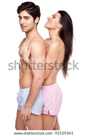 Smiling woman standing behind her partner caressing his chest, both topless, studio on white