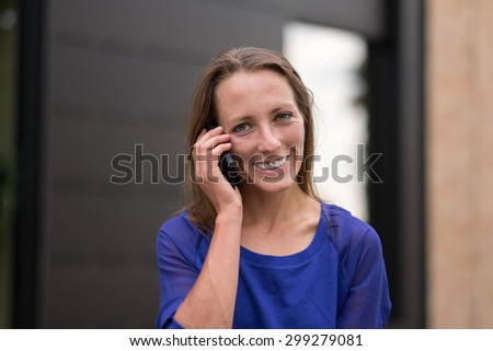 Smiling woman standing in front of a building listening to a call on her mobile phone, head and shoulders - stock photo