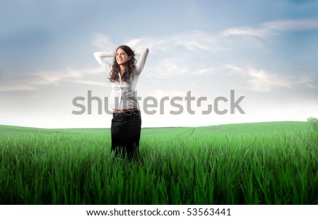 Smiling woman standing on a green meadow - stock photo