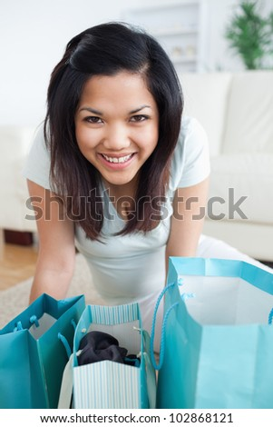 Smiling woman standing over shopping bags in a living room - stock photo