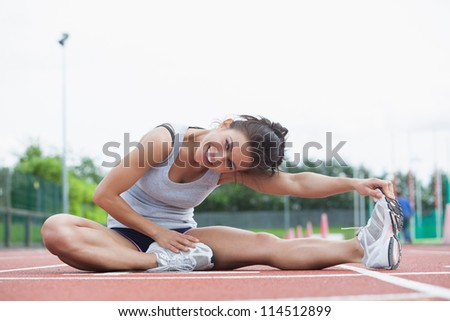 Smiling woman stretching her legs on a track - stock photo