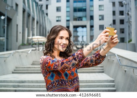 Smiling woman taking a selfie photo in an urban street. Beautiful curly caucasian brunette girl in a dress with a print makes selfie. Woman on the background of the business center. A tourist. - stock photo
