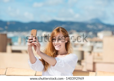 Smiling woman taking her photograph using a mobile phone and smiling as she poses for the picture - stock photo