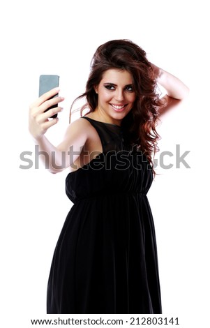 Smiling woman taking self picture with smartphone camera - stock photo