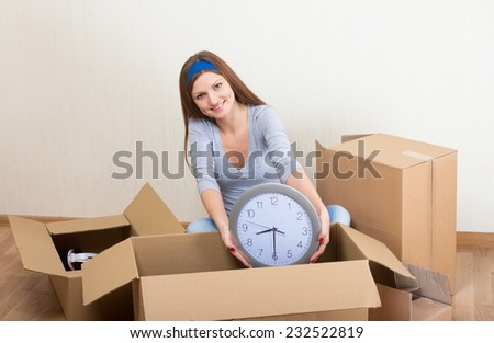 Smiling woman taking the clock from moving box - stock photo