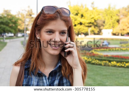 Smiling woman talking on the phone - stock photo