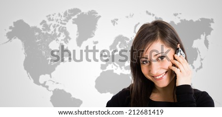 Smiling woman talking on the phone in front of a world map - stock photo
