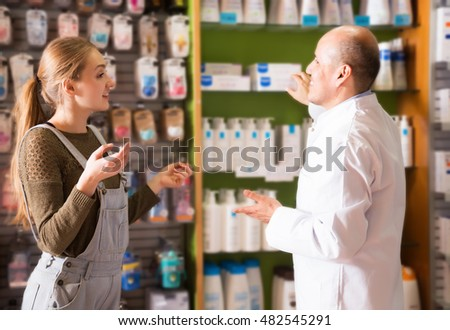 Smiling woman talking to a pharmacist in a pharmacy