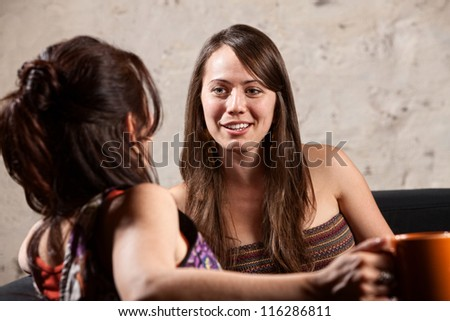 Smiling woman talking with a friend sitting indoors talking - stock photo