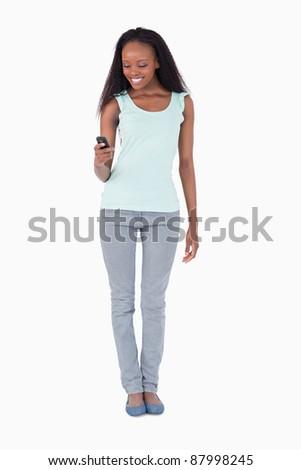 Smiling woman texting on white background - stock photo