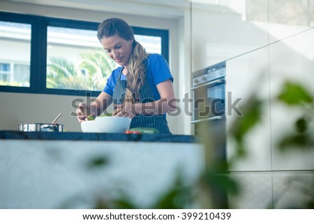 smiling woman tossing a salad for dinner in the kitchen