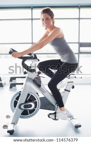 Smiling woman training on exercise bike in gym