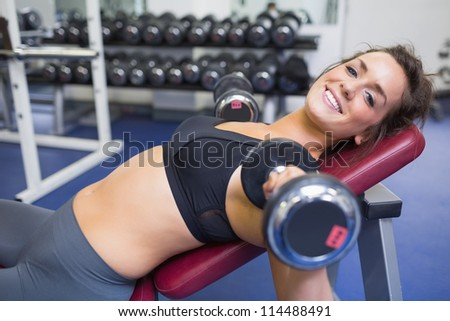 Smiling woman training with weights in gym - stock photo