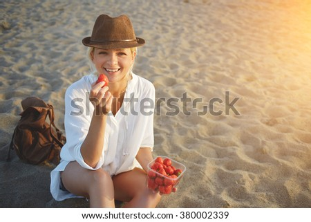 Smiling woman traveler with backpack enjoying strawberries while sitting on sand beach in sunny summer day, cheerful attractive female in stylish hat eating fruits during rest after walking near sea - stock photo