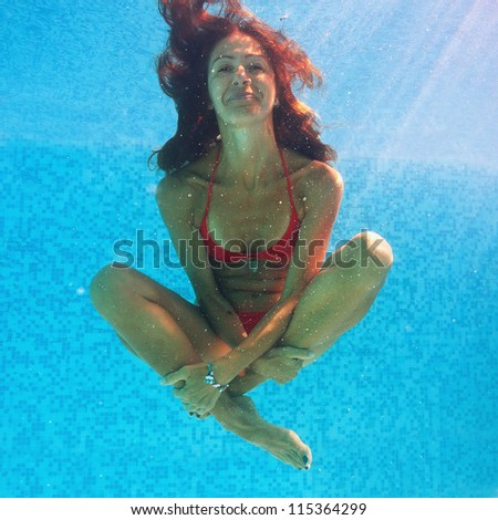 Smiling woman underwater close up portrait in swimming pool.