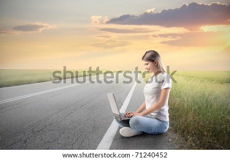 Smiling woman using a laptop on a countryside road - stock photo