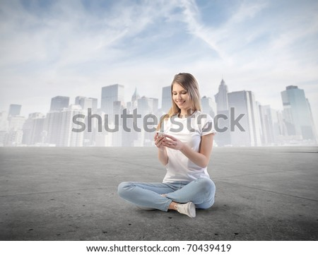 Smiling woman using a mobile phone with cityscape on the background
