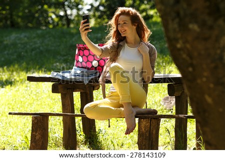 Smiling woman  using a smart phone and relaxing at the park.Doing selfie. - stock photo