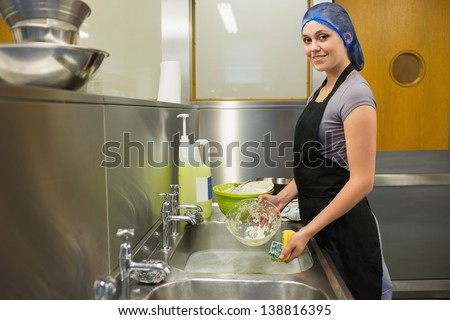 Smiling woman using a sponge in the restaurant - stock photo