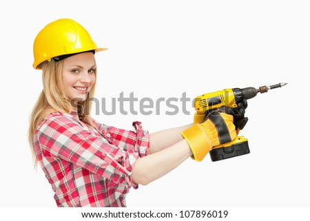 Smiling woman using an electric screwdriver against white background - stock photo
